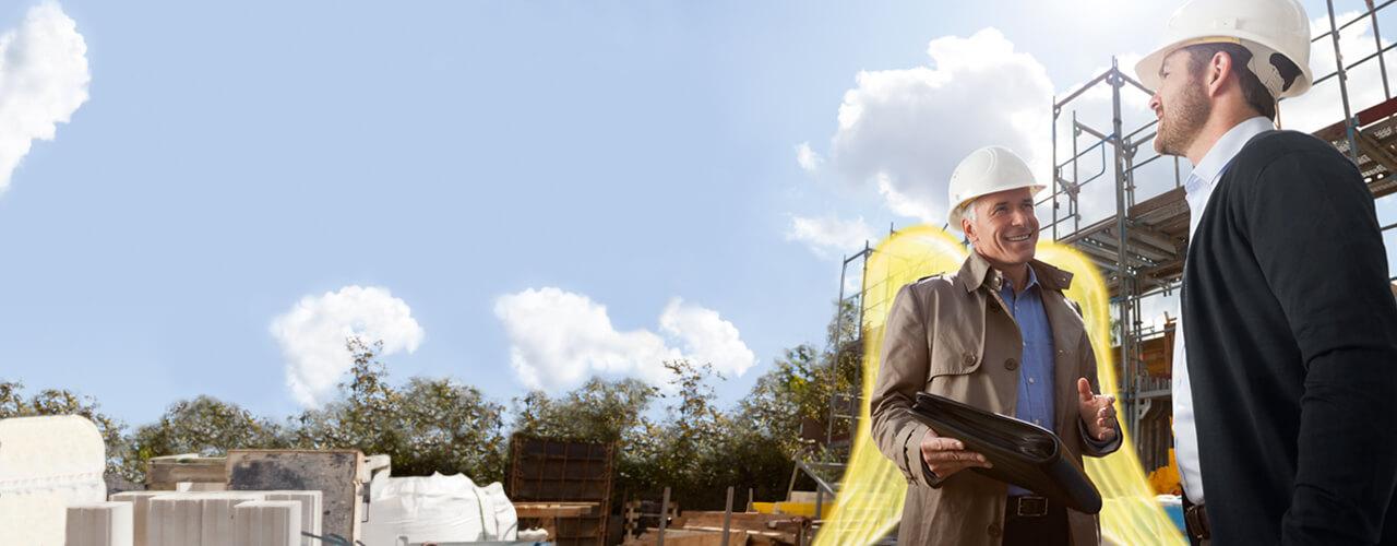 Bauleistungsversicherung: Ein Versicherungsexperte mit Schutzengel-Flügeln und ein Bauherr stehen auf einer Baustelle und besprechen Details.